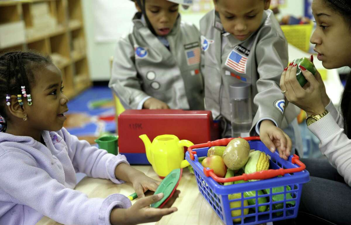 Oumou Balde (left) plays with her teacher Jacqualine Sanchez and some pretend food in a New York prekindergarten class designed to educate kids about nutrition and health.