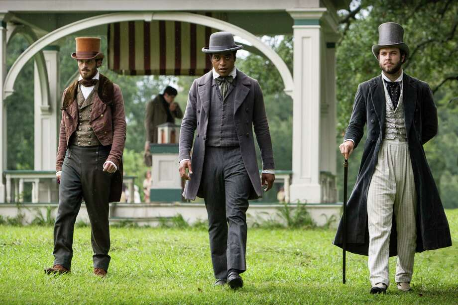 "Chiwetal Ejiorfor, as Solomon Northup, center, strolls through a close representation of Congress Park with Scoot McNairy, left, as Brown, and Taran Killam, right, as Hamilton,€""the two men who lured Solomon from Saratoga to play the violin at a circus in Washington, D.C., then sold him into slavery, in the Steve McQueen film ""12 Years a Slave."" (Courtesy of Fox Searchlight) Photo: Jaap Buitendijk / Digital / 35mm"