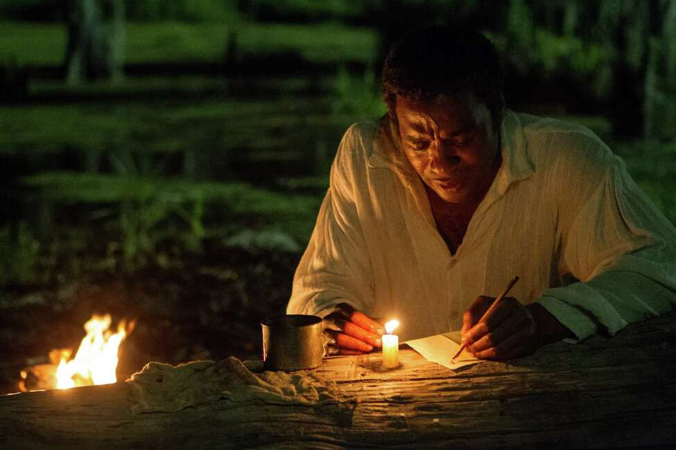 Solomon Northup, portrayed by Chiwetel Ejiofor, crafts a letter with a crude handmade pen and ink in