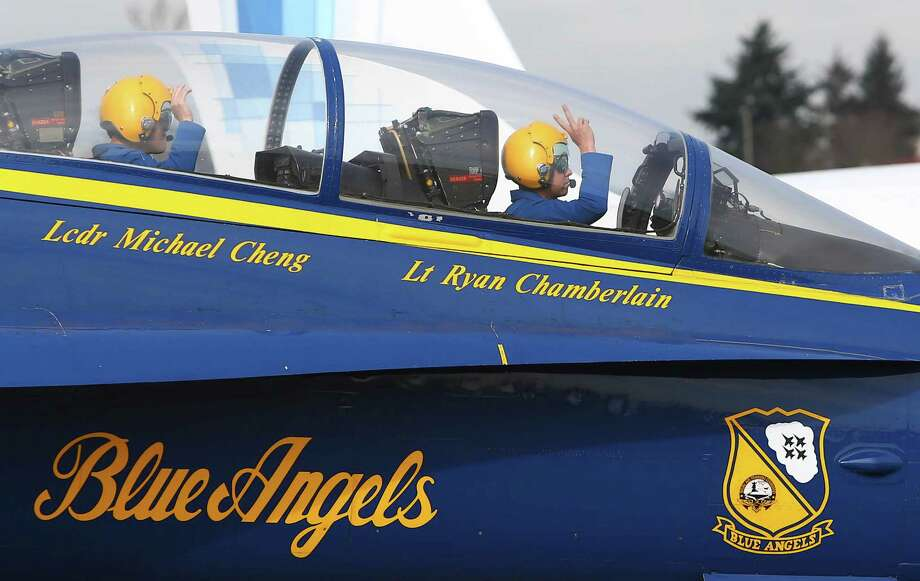 Lt. Cdr. Michael Cheng and Lt. Ryan Chamberlain wave from the cockpit as Blue Angels airplane number seven makes a stop in Seattle on Thursday, February 27, 2014 at Boeing Field. The two members of the U.S. Navy high performance aerial team were in Seattle to plan their visit for Seafair this summer. The Blue Angels are returning to Seattle in 2014 after federal government budget sequestration grounded the aerial performance team in 2013. Chamberlain said pilots were kept current with flight training and the aircraft maintained, but they did not train for their high performance routines. Photo: JOSHUA TRUJILLO, SEATTLEPI.COM / SEATTLEPI.COM