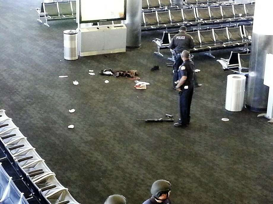 Police stand near a weapon at Los Angeles International Airport after a gunman opened fire in November, killing one person and wounding several others. Photo: Associated Press