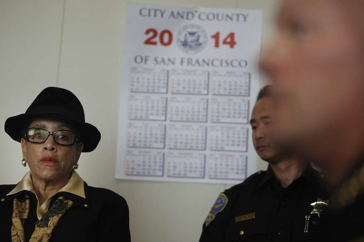 Joyce Hicks (left), San Francisco Office of Citizen Complaints director listens as San Francisco Police Chief Greg Suhr (right partially seen blurred) speaks during a press conference regarding the five San Francisco police officers and one former San Francisco police officer who have been indicted by a federal grand jury at the Hall of Justice on Thursday, February 27, 2014 in San Francisco, Calif.