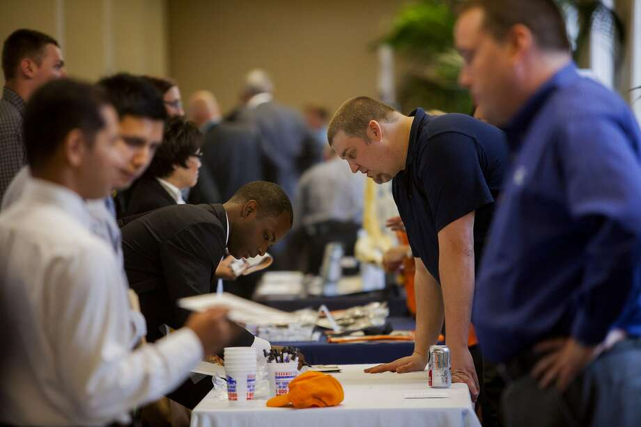 Job seekers speak with representatives at the RecruitMilitary veteran job fair in San Diego in February. Photo: Sam Hodgson, Bloomberg