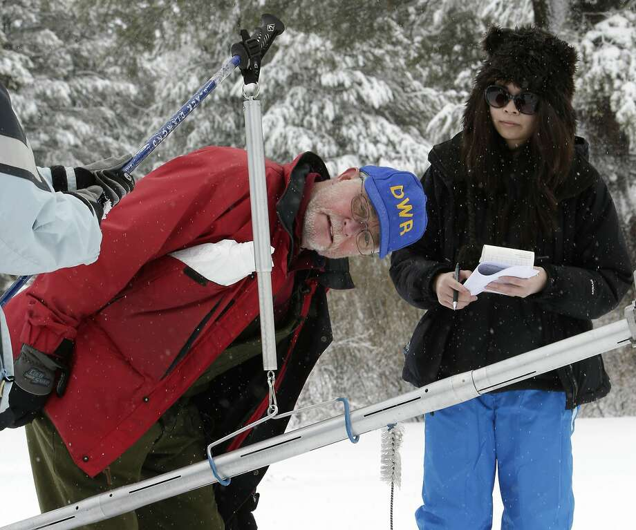 Gehrke reads the snowpack weight to California Council on Science and Technology Policy Fellow Toni Lee, who accompanied him on the snow survey. Photo: Rich Pedroncelli, Associated Press
