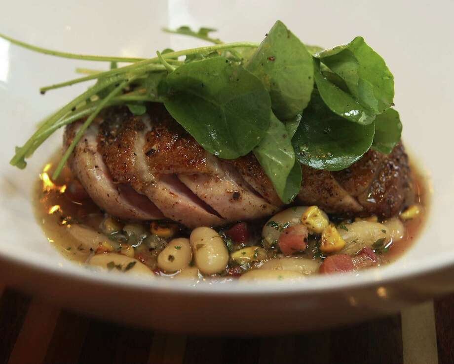 A seared and seasoned duck breast sits atop a mixture of white beans, pancetta and charred corn and is topped with lightly dressed watercress. Photo: Photos By Kin Man Hui / San Antonio Express-News / ©2013 San Antonio Express-News