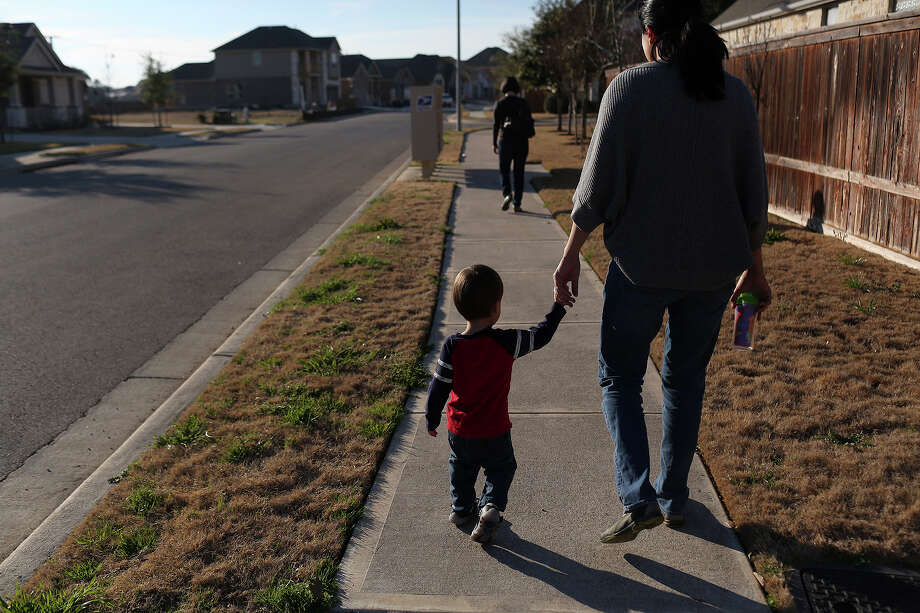 Cleo DeLeon holds her son's hand while they walk to check the mail with her wife, Nicole Dimetman, in Austin on Saturday, Feb. 8, 2014. Photo: Lisa Krantz, San Antonio Express-News / San Antonio Express-News