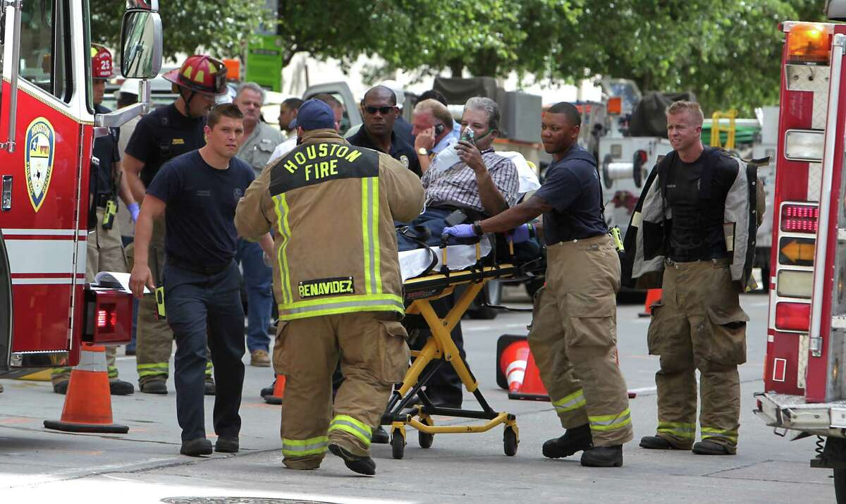 Houston Fire Department fire fighters prepare to transport an injured man to a hospital at the scene of an electrical vault fire at a building in the 1100 block of Capital Thursday, June 20, 2013, in Houston. Five workers were transported to area hospitals with unknown injuries. ( James Nielsen / Houston Chronicle )
