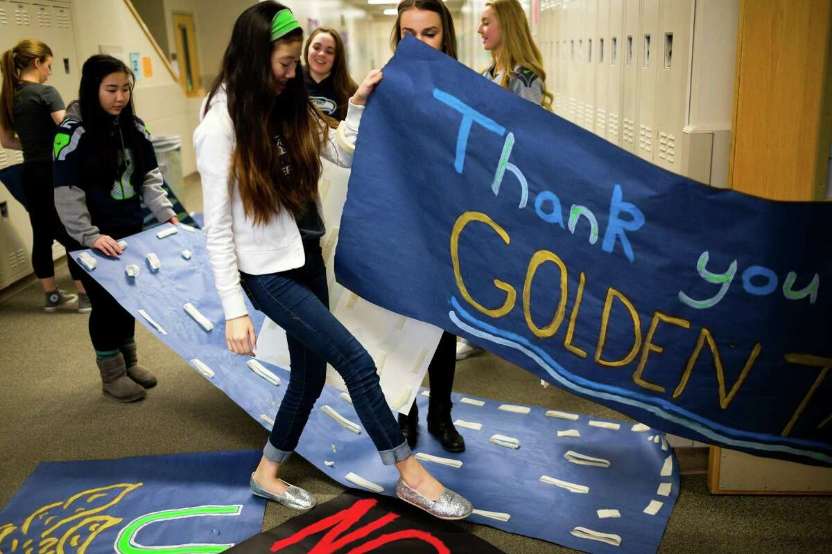 Auburn Riverside High School students craft signs before the arrival of Seahawks wide receiver Golden Tate for the Verizon-sponsored second annual ?'Save It Seattle?