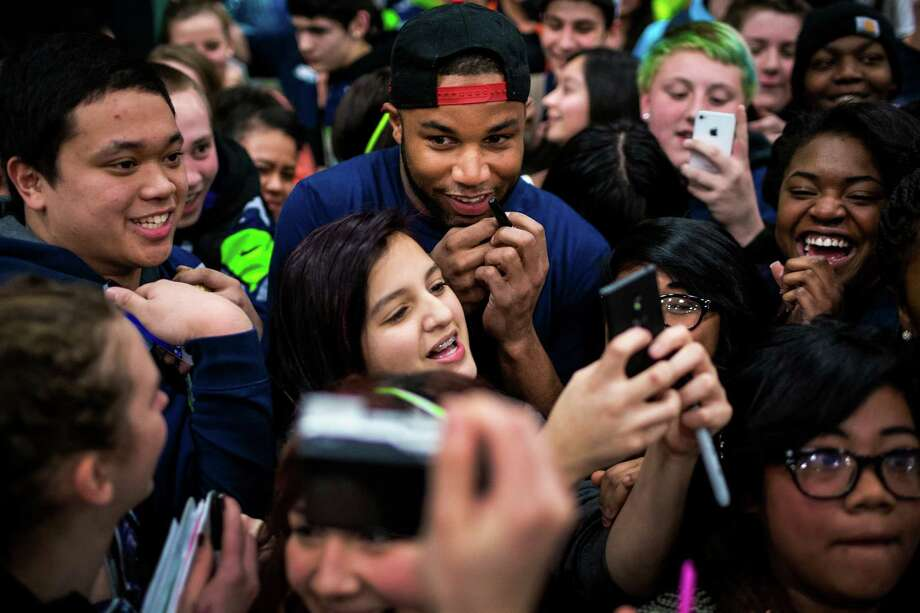 "Seahawks wide receiver Golden Tate is mobbed by hundreds of students at Auburn Riverside High School after the institution won the Verizon-sponsored second annual ÒSave It SeattleÓ contest Thursday, Feb. 27, 2014, in Auburn. The ""Save It Seattle"" movement encourages the community to take a pledge to stop texting and driving. Quarterback Russell Wilson was the guest last year after Seattle's Roosevelt High School won the contest. Photo: JORDAN STEAD, SEATTLEPI.COM / SEATTLEPI.COM"