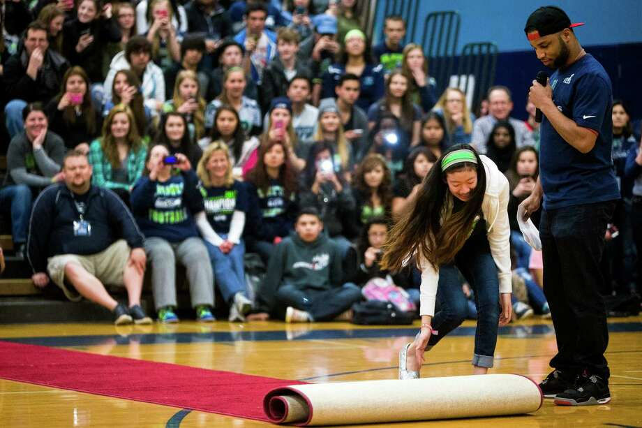 "Seahawks wide receiver Golden Tate, right, watches a student roll out a red carpet for him during an assembly at Auburn Riverside High School after the institution won the Verizon-sponsored second annual ÒSave It SeattleÓ contest Thursday, Feb. 27, 2014, in Auburn. The ""Save It Seattle"" movement encourages the community to take a pledge to stop texting and driving. Quarterback Russell Wilson was the guest last year after Seattle's Roosevelt High School won the contest. Photo: JORDAN STEAD, SEATTLEPI.COM / SEATTLEPI.COM"