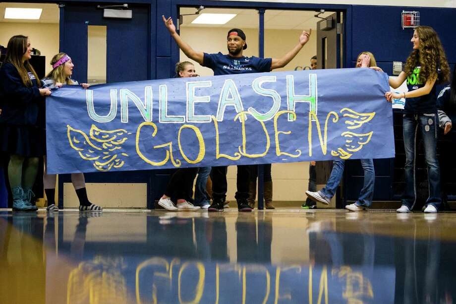 "Seahawks wide receiver Golden Tate, center, prepares to break through a banner for him during an assembly at Auburn Riverside High School after the institution won the Verizon-sponsored second annual ÒSave It SeattleÓ contest Thursday, Feb. 27, 2014, in Auburn. The ""Save It Seattle"" movement encourages the community to take a pledge to stop texting and driving. Quarterback Russell Wilson was the guest last year after Seattle's Roosevelt High School won the contest. Photo: JORDAN STEAD, SEATTLEPI.COM / SEATTLEPI.COM"