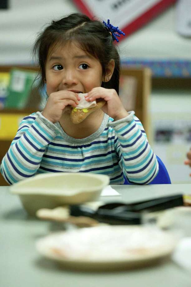 Deziree Ramirez, 3, center, eats an afternoon snack of turkey meat on a slice of low-fat bread after the children ate tofu and sweet potato french fries for their lunch at the Harris County Department of Education Head Start program in the 5th Ward Multiservice Center. Photo: Johnny Hanson, Houston Chronicle / © 2014  Houston Chronicle