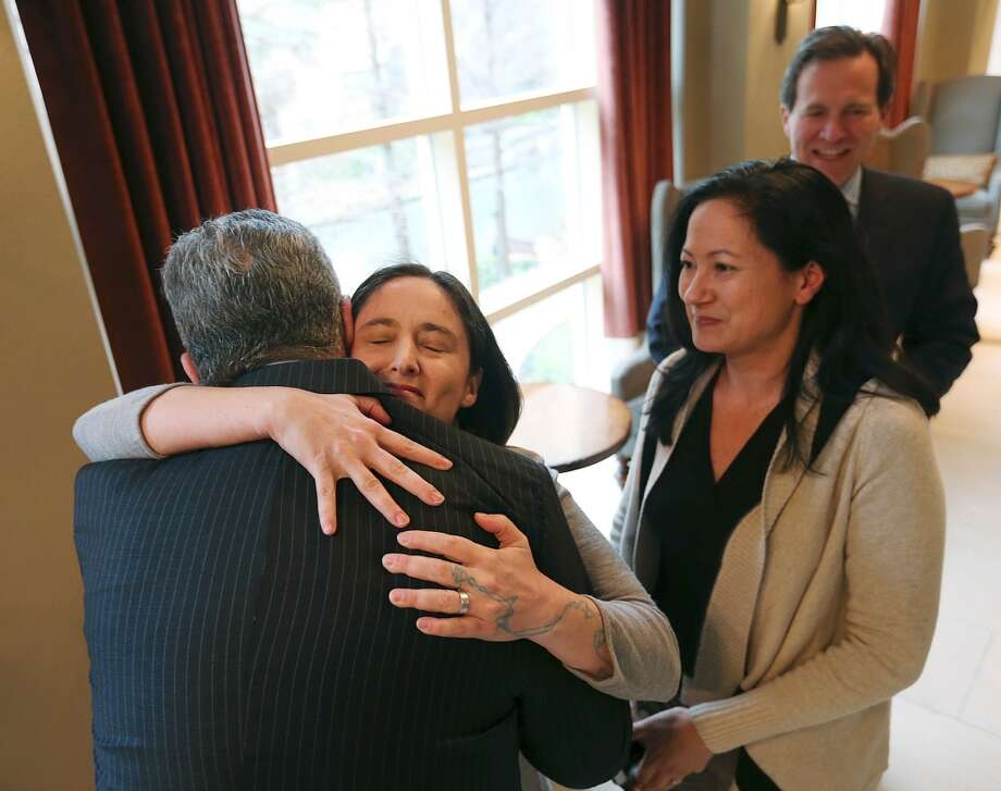 Nicole Dimetman hugs attorney Barry Chasnoff as her partner, Cleopatra De Leon, waits to greet him before a press conference in San Antonio on Wednesday, Feb. 26, 2014, after U.S. Federal Judge Orlando Garcia declared a same-sex marriage ban in deeply conservative Texas unconstitutional. Garcia said the couples are likely to win their case and the ban should be lifted, but said he would not enforce his ruling pending one by the 10th Circuit Court of Appeals, which already is hearing two other states' cases. He also will give Texas time to appeal to the 5th Circuit Court of Appeals in New Orleans. (AP Photo/San Antonio Express-News, Jerry Lara) MAGS OUT; TV OUT; NO SALES; SAN ANTONIO OUT; RUMBO DE SAN ANTONIO OUT; MANDATORY CREDIT: Photo: Associated Press