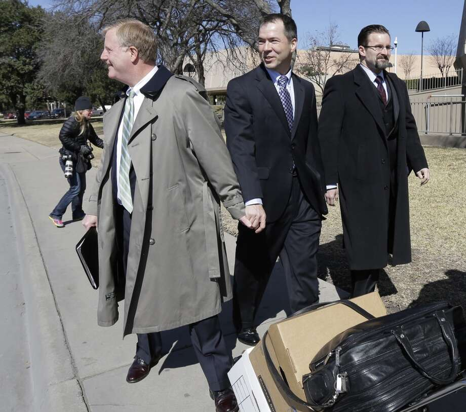 Mark Phariss, left, holds the hand of partner Victor Holmes, center, as they leave the U.S. Federal Courthouse, Wednesday, Feb. 12, 2014, in San Antonio. District Judge Orlando Garcia said Wednesday he would issue a decision later after the two Texas men filed a civil rights lawsuit seeking permission to marry, and a lesbian couple sued to have their marriage recognized. (AP Photo/Eric Gay) Photo: Associated Press
