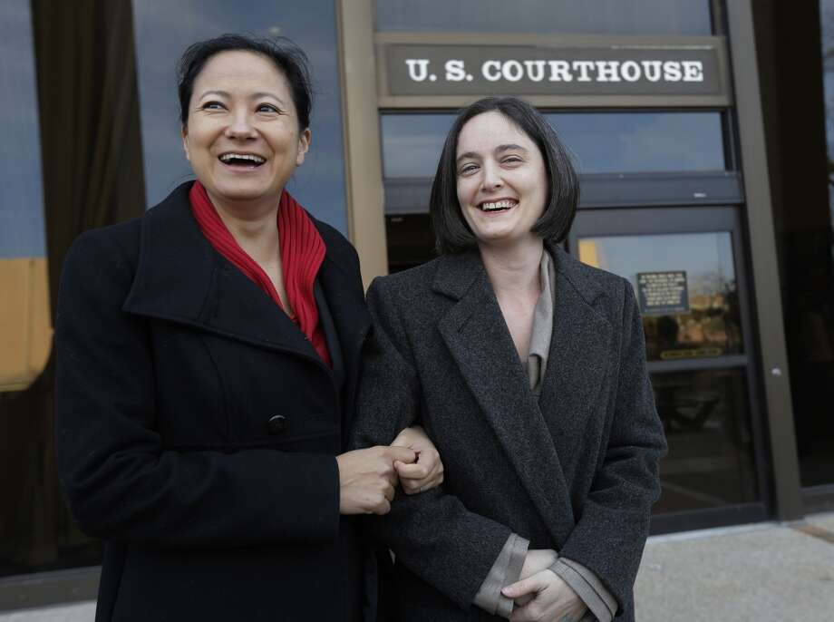 In this Feb. 12, 2014 file photo, Cleopatra De Leon, left, and partner, Nicole Dimetman, right, arrive at the U.S. Federal Courthouse, in San Antonio, where a federal judge is expected to hear arguments in a lawsuit challenging Texas' ban on same-sex marriage. On Wednesday, Feb. 26, 2014, Judge Orlando Garcia has struck down  the ban but is leaving it in place pending a ruling by an appeals court later this year. (AP Photo/Eric Gay, File) Photo: Associated Press