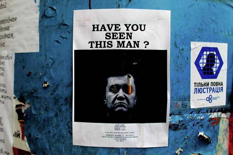 A poster with a photo of fugitive Ukrainian President Viktor Yanukovych, who fled the capital Kiev and went into hiding after months of protests against his government, is seen on a barricade in Kiev. Photo: Marko Drobnjakovic, STR / AP