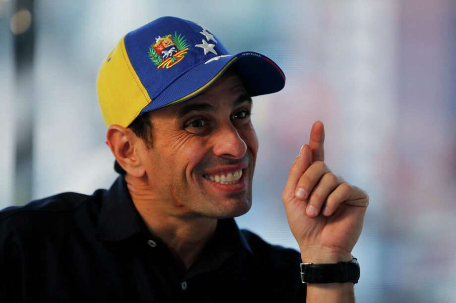 In this Feb. 25, 2014 photo, Opposition leader and Mirada's State governor Henrique Capriles gestures during an interview at his office in Caracas, Venezuela. Capriles says the opposition has put its differences over strategy behind them, adding that the government may have miscalculated its response to the protests as well. (AP Photo/Fernando Llano) Photo: Fernando Llano, STF / AP