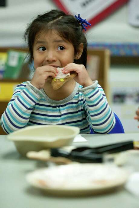 Deziree Ramirez, 3, eats a turkey snack at a 5th Ward Head Start program. The obesity rate in kids like her has dropped 40 percent in less than a decade. Photo: Johnny Hanson, Staff / © 2014  Houston Chronicle