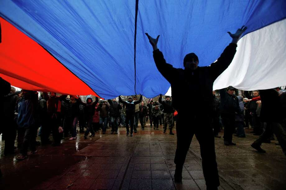 Pro-Russian activists march Thursday with a huge Russian flag in Simferopol, Crimea, Ukraine. Police and Ukrainian troops were on high alert after dozens of masked men seized government buildings in the Crimea. Photo: Darko Vojinovic, STF / AP