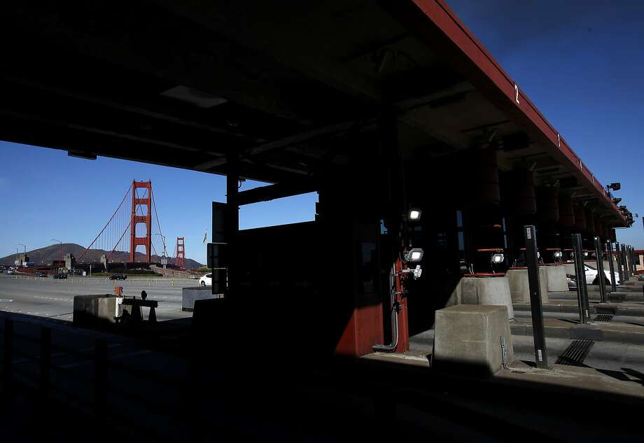 With the Golden Gate Bridge in the background Monday, vehicles pass through the toll plaza in San Francisco. Photo: Sarah Rice, Special To The Chronicle