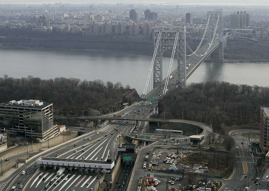 In this Dec. 1, 2013 file aerial photo, the tollbooth lanes, lower left, lead to the George Washington Bridge in Fort Lee, N.J. Many people have known little about Fort Lee until a political scandal centering on New Jersey Gov. Chris Christie enveloped the borough. Now for residents of the New York City bedroom community defined by both a feisty pride and frustration over the mixed blessings of proximity to the George Washington Bridge, the scandal is the reminder they did not need of how the bridge dictates the rhythm of everyday life.  (AP Photo/Mark Lennihan, File) Photo: Mark Lennihan, Associated Press