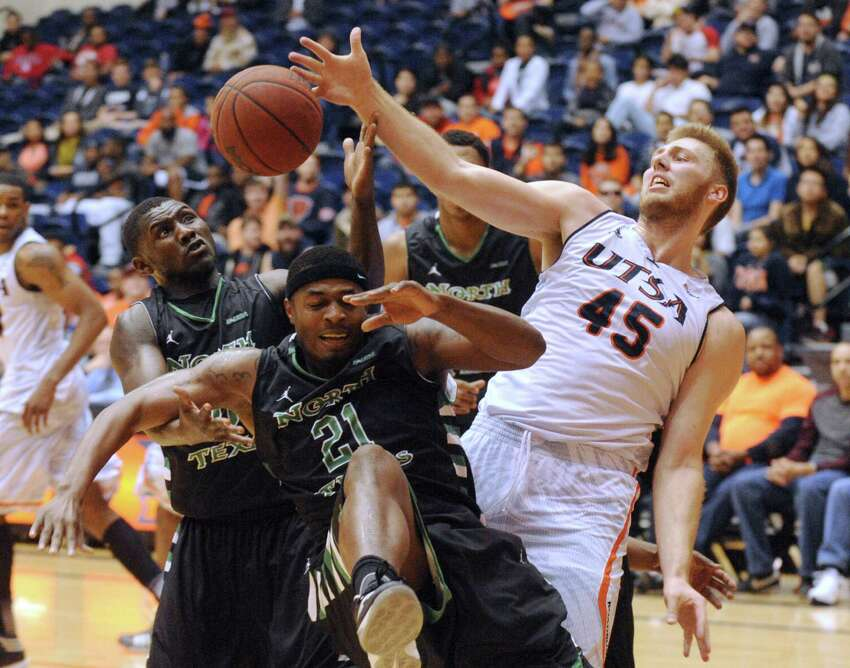 Kaj-Björn Sherman of UTSA, right, battles for a loose ball against T. J. Taylor (21) and Vertrall Vaughns of North Texas during college basketball action at the UTSA Convocation Center on Thursday, Feb. 27, 2014.