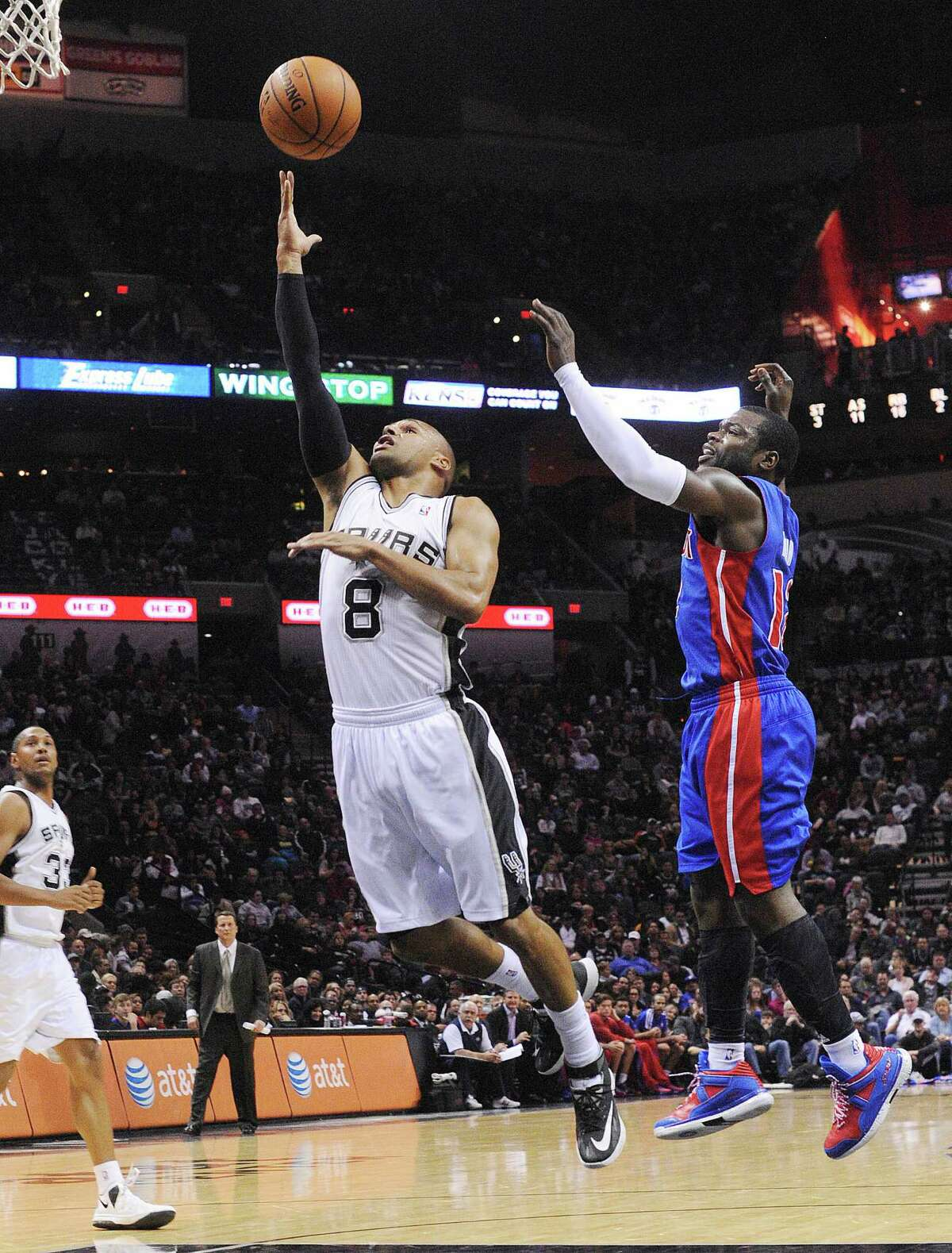 Patty Mills (8) of the San Antonio Spurs lays up the ball as Will Bynum of the Detroit Pistons defends during NBA action in the AT&T Center on Wednesday, Feb. 26, 2014.
