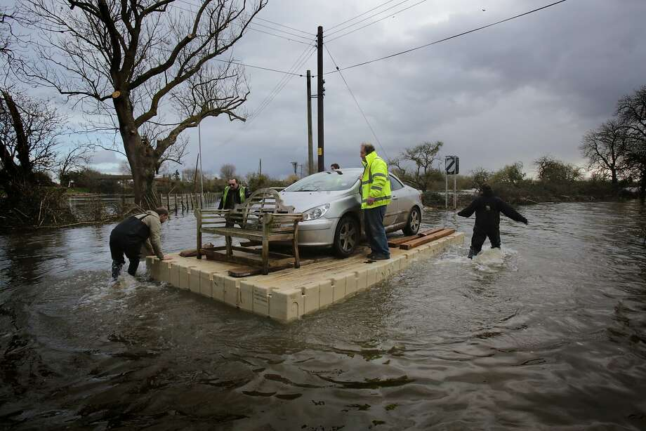 BURROWBRIDGE, UNITED KINGDOM - FEBRUARY 27:  Volunteers use a pontoon to move a car that has been cut off by flood waters at Burrowbridge on the Somerset Levels on February 27, 2014 in Somerset, England.  According to the Met Office, England and Wales have experienced their wettest winter since records began in 1766, with parts of flood-hit southern England having experienced 83% more rain than average.  (Photo by Matt Cardy/Getty Images) *** BESTPIX *** Photo: Matt Cardy, Getty Images