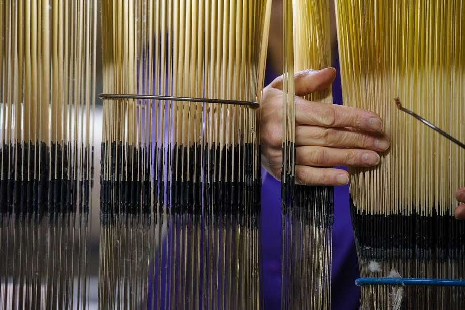 An employee works with a weaving loom at the Garnier-Thiebaut linen maker factory on February 27, 2014, in Gerardmer, eastern France.   TOPSHOTS / AFP PHOTO / SEBASTIEN BOZONSEBASTIEN BOZON/AFP/Getty Images Photo: Sebastien Bozon, AFP/Getty Images