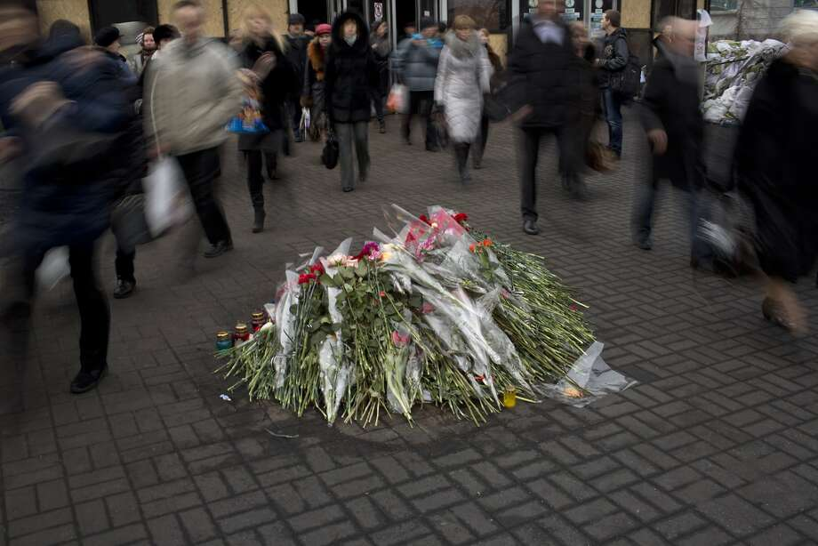 People walk past flowers placed on the ground near a memorial for the people killed in clashes with the police, at Kiev's Independence Square, the epicenter of the country's current unrest, Ukraine,  Thursday, Feb. 27, 2014. Ukraine put its police on high alert after dozens of armed pro-Russia men stormed and seized local government buildings in Ukraine's Crimea region early Thursday and raised a Russian flag over a barricade. (AP Photo/Emilio Morenatti) Photo: Emilio Morenatti, Associated Press