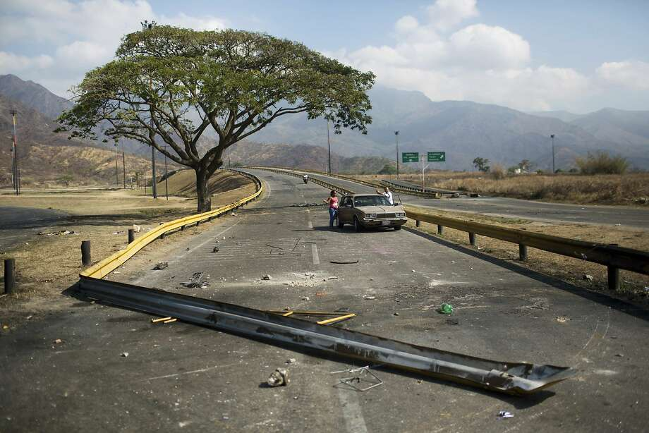 A guardrail turned into a barricade by protesters blocks a couple's car in Valencia, Venezuela. In the past two weeks, clashes between protesters and security forces loyal to the president have left 16 dead, and opposition leader Leopoldo Lopez has been thrown in 