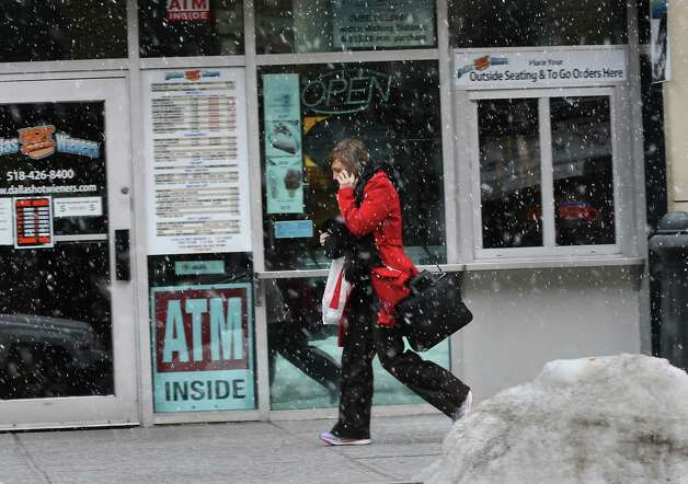 A woman talks on her cell phone while walking down South Pearl St. in a snow squall on Thursday, Feb. 27, 2014 in Albany, N.Y.  (Lori Van Buren / Times Union) Photo: Lori Van Buren / 00025939A