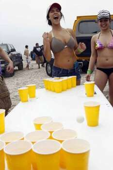 Sarah Martinez reacts as her ping pong ball bounces off one of the cups March 12, 2012, with Mariah Mandel, right, during the first day of spring break on Padre Island in Corpus Christi. (Michael Zamora / Associated Press)