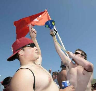"""Jace Head cheers on Michael Latimer as he drinks beer from a """"beer bong"""" March 14, 2008, in South Padre Island. (Billy Smith II / Houston Chronicle)"""