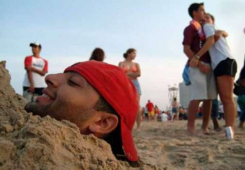 Khalil Abdullah, a student from UT Pan-American University in Edinburg, was buried up to his head by his friends on South Padre Island on March 14, 2003. (Rex C. Curry / Special to the Chronicle)