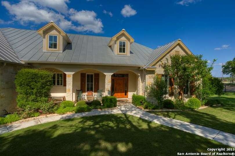 This beautiful landscaped stone stucco home features for Texas hill country stone homes