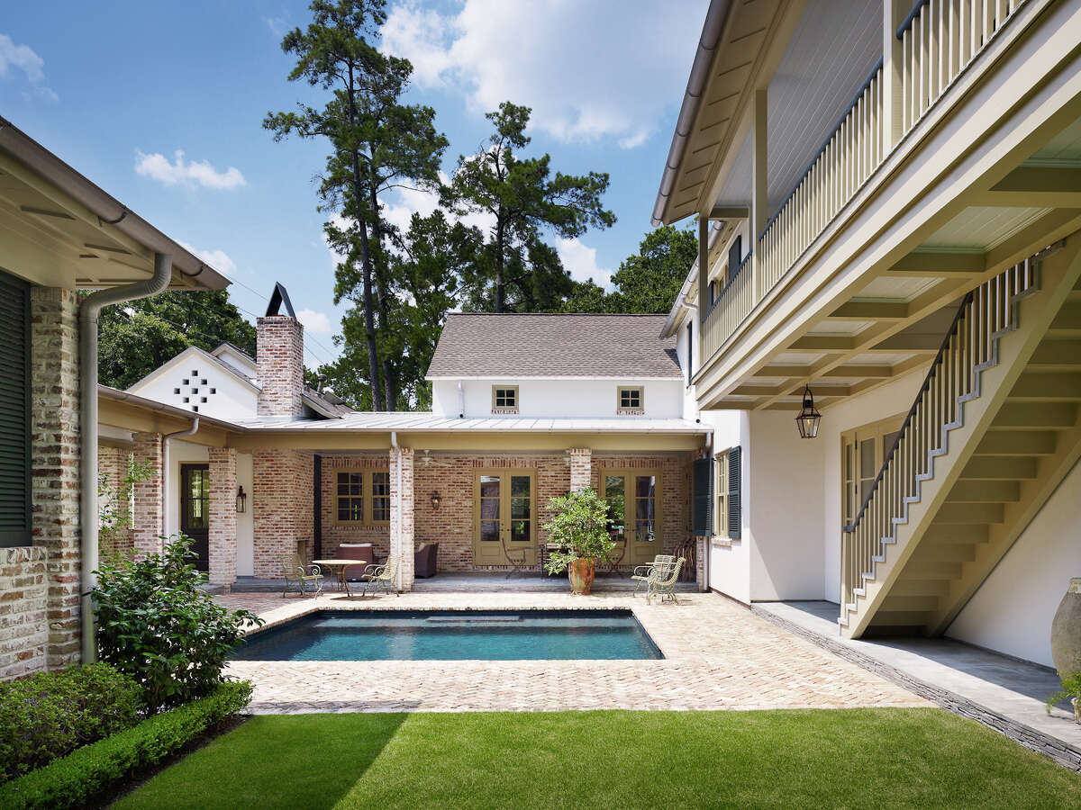 Chicago brick decking, laid in a herringbone pattern, surrounds the square pool in the courtyard.