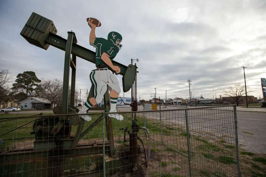 In the First Baptist Church parking lot, a few feet away from a rusty basketball hoop that looks just as old as the well, a pump jack quarterback is poised to make a pass. The quarterback is wearing Luling High School's green and white. Photo: Todd Wiseman, TexasTribune.org
