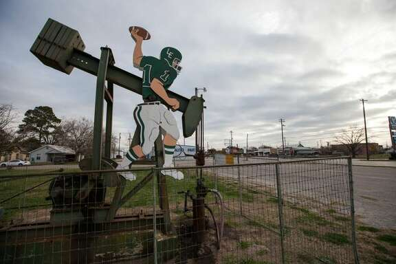 In the First Baptist Church parking lot, a few feet away from a rusty basketball hoop that looks just as old as the well, a pump jack quarterback is poised to make a pass. The quarterback is wearing Luling High School's green and white.