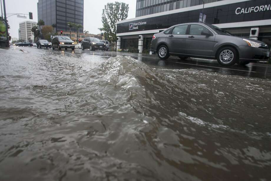 Motorists drive by a flooded portion of Ventura Blvd., in Sherman Oak, section of Los Angeles Friday, Feb. 28, 2014.  The first wave of a powerful Pacific storm spread rain and snow early Friday through much of California, where communities endangered by a wildfire just weeks ago now faced the threat of mud and debris flows.  Photo: Ringo H.W. Chiu, Associated Press