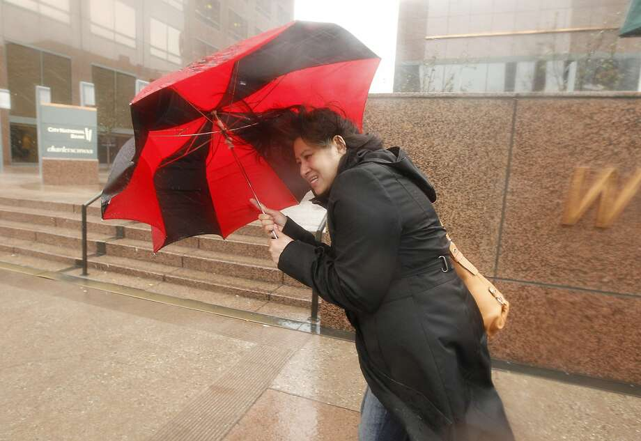 A pedestrian blocks the heavy winds with her umbrella in Los Angeles, Friday, Feb. 28, 2014.  The first wave of a powerful Pacific storm spread rain and snow early Friday through much of California, where communities endangered by a wildfire just weeks ago now faced the threat of mud and debris flows.  Photo: Damian Dovarganes, Associated Press