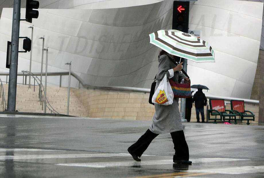A pedestrian covers from the rain as she makes her way past the Disney Music Center in downtown Los Angeles on Friday, Feb. 28, 2014. The first wave of a powerful Pacific storm spread rain and snow early Friday through much of California, where communities endangered by a wildfire just weeks ago now faced the threat of mud and debris flows. Photo: Richard Vogel, Associated Press