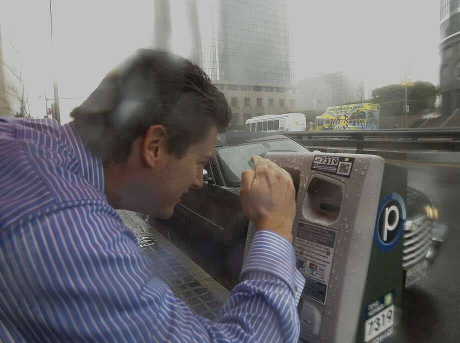 A motorist struggles to read an electronic display of parking meter under heavy rain in downtown Los Angeles Friday, Feb. 28, 2014. A strong Pacific storm has brought rain and snow to much of California.  Photo: Damian Dovarganes, Associated Press