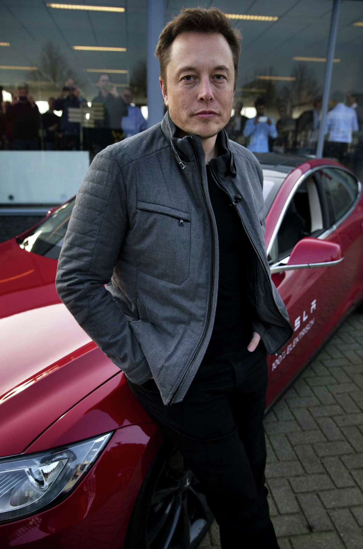 Elon Musk, co-founder and CEO of American electric vehicle manufacturer Tesla Motors, poses with a Tesla during a visit to Amsterdam on January 31, 2014. The European Tesla Service is based in Tilburg and the European headquarters is in Amsterdam. AFP PHOTO / ANP/ JERRY LAMPEN --NETHERLANDS OUT--JERRY LAMPEN/AFP/Getty Images