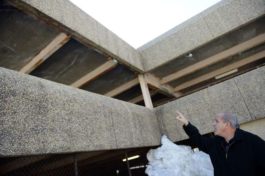 Derby Alderman Carmen DiCenso points out damaged areas of the Derby parking garage Friday, Feb. 28, 2014.  The Derby Board of Alderman Thursday night ordered the municipal parking garage closed until further notice for safety reasons. Photo: Autumn Driscoll / Connecticut Post