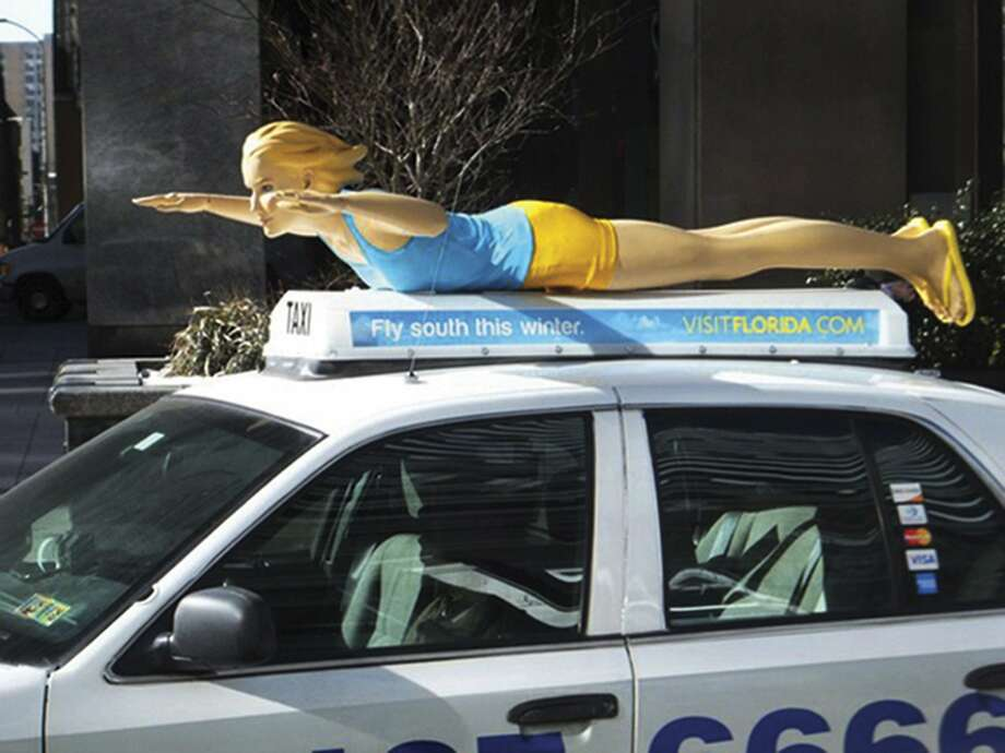 A fiberglass mannequin atop a taxi in Philadelphia promotes the warmth of Florida as winter grips the Midwest and Northeast. Photo: Uncredited, Associated Press