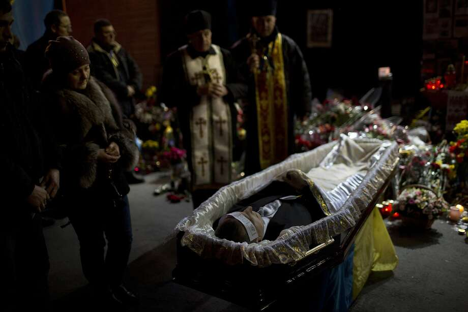 The body of anti-Yanukovych protester Bailuk Alexander, 40, killed in a recent clash with riot police in Kiev's Independence Square, is seen in a coffin during his funeral on Friday, Feb. 28, 2014, in Ukraine. Official reports say 82 people were killed in severe clashes between opposition activists and riot police. (AP Photo/Emilio Morenatti) Photo: Emilio Morenatti, Associated Press