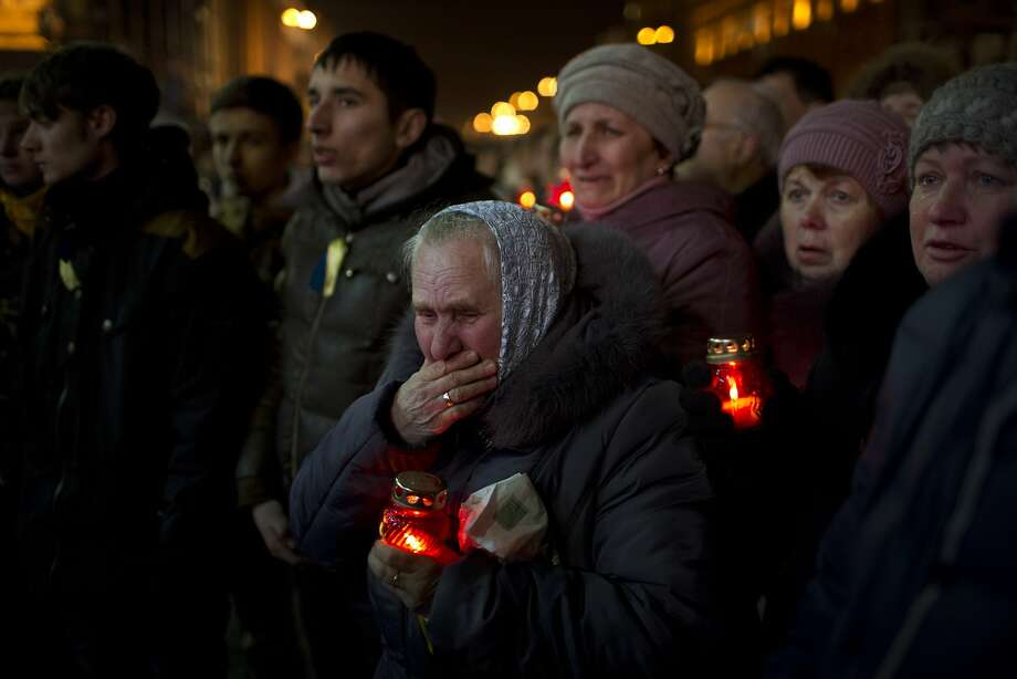 People react during the funeral of anti-Yanukovych protester Bailuk Alexander, 40, killed in a recent clash with riot police in Kiev's Independence Square, Ukraine, Friday, Feb. 28, 2014. Official reports say 82 people were killed in severe clashes between opposition activists and riot police. (AP Photo/Emilio Morenatti) Photo: Emilio Morenatti, Associated Press