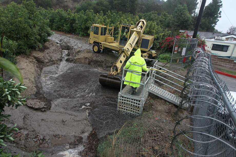 Workers clear debris from a drainage as a storm brings rain in the midst of record drought on February 28, 2014 in Glendora, California. The rain offers some relief to the dry conditions but is not expected to be enough to break the historic drought. A drought-related unseasonal wildfire, the Colby Fire, was accidentally ignited in the dry chaparral vegetation in January, destroying homes and sending thousands fleeing. The charred and denuded hillsides are threatening the homes of about a thousand evacuated residents with rain-loosened mud-ash debris flows. Photo: David McNew, Getty Images