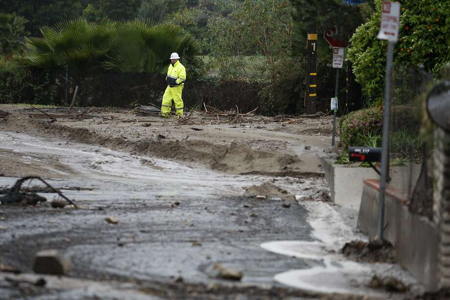 A worker surveys a debris-filled street below the Colby Fire burn area as a storm brings rain in the midst of record drought on February 28, 2014 in Glendora, California. The rain offers some relief to the dry conditions but is not expected to be enough to break the historic drought. A drought-related unseasonal wildfire, the Colby Fire, was accidentally ignited in the dry chaparral vegetation in January, destroying homes and sending thousands fleeing. The charred and denuded hillsides are threatening the homes of about a thousand evacuated residents with rain-loosened mud-ash debris flows.  Photo: David McNew, Getty Images